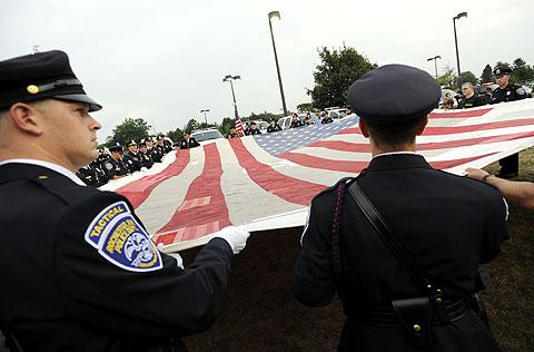Rochester police officers hold the National 9/11 Flag.