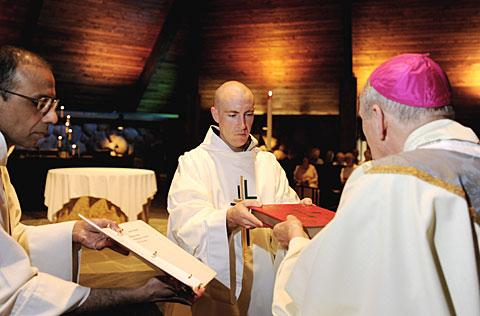 Bishop Clark (right) hands the Book of Gospels to Brother Slater.