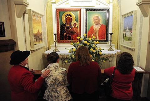 Parishioners kneel to pray at a shrine to Pope John Paul II.