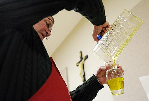 Deacon Lynn Kershner pours Oil of the Sick into vessels.