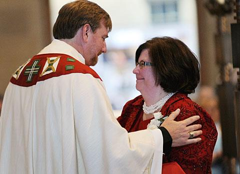 Bonnie Caton hugs her husband after he received his vestments.