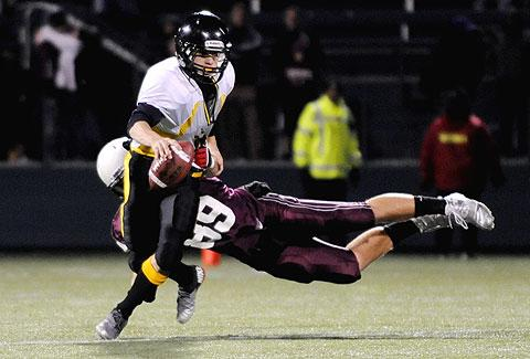 Peter DiLaura dives for McQuaid QB Charlie Meagher.