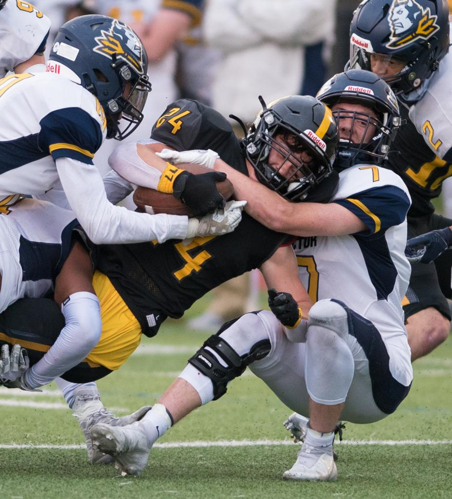 McQuaid running back Jack Miller is brought down by Victor's Trenton Sherman (right).