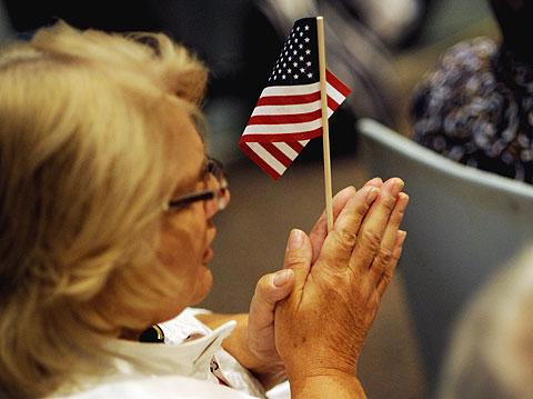 Fran McCarthy holds a flag as she prays.