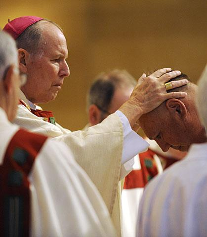 Bishop Clark imposes his hands on Robert Lyons.