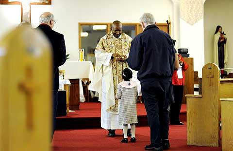 Father Paul Gitau distributes Communion during the Mass.