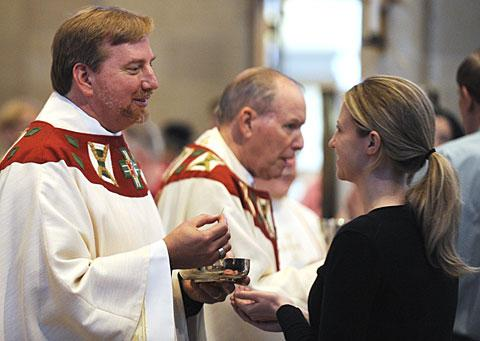 Father Caton offers communion to his daughter Emily Volpe.