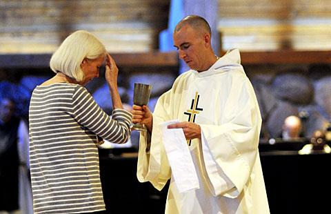 Brother Slater serves as a eucharistic minister during Mass.