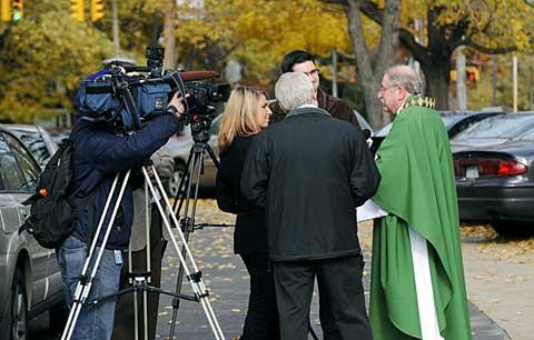 Father Norman Tanck talks to media members after the Mass.