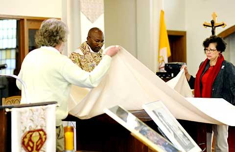 Father Gitau and parishioners remove the altar cloth.