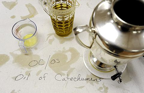 A stained tablecloth near the Oil of Catechumens.