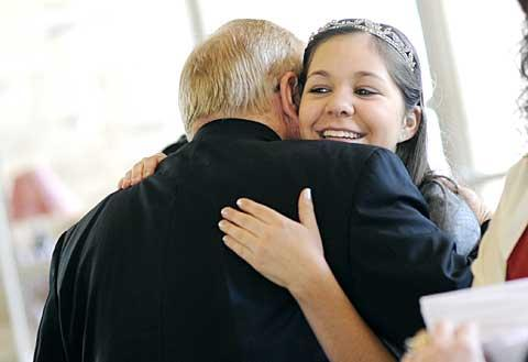 Natalie is congratulated by Father James Schwartz.