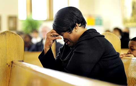 Parishioner Jané Cooper cries at the conclusion of the Mass.