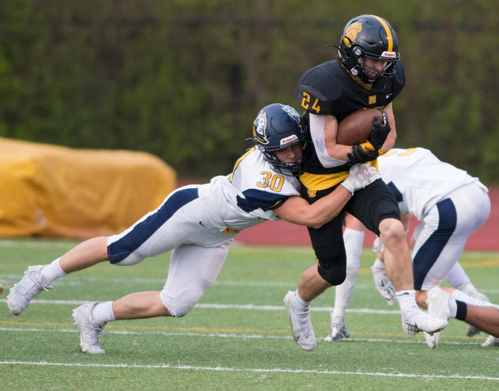 McQuaid running back Jack Miller (right) is stopped by Victor's Casey John Keohane (left).