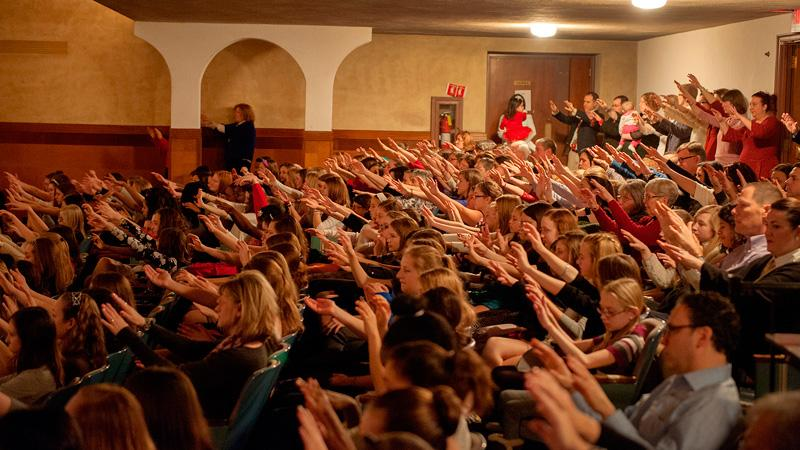 Students, staff, family and alumni raise their hands in blessing during the Dec. 20 Golden Mass.