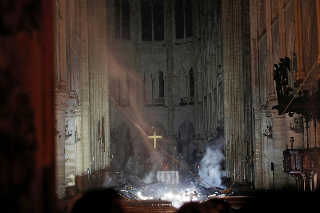 Smoke rises around the altar inside Notre Dame Cathedral in Paris as a fire continues to smolder early April 16. (CNS photo by Philippe Wojazer, Reuters)
