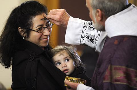 Helen Arco and daughter Abriele receive ashes.