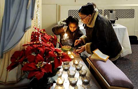 Léciana Dominguez, 6, lights a candle after Mass.