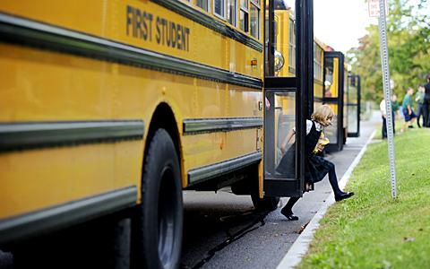 Students arrive on buses for the Mass.
