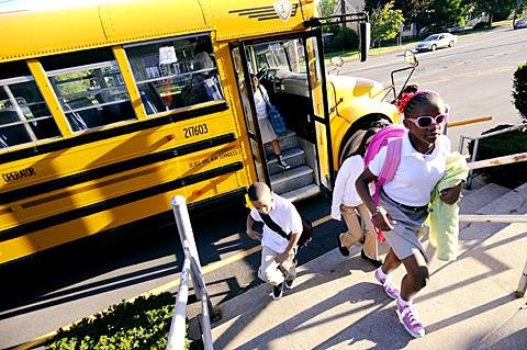 Stylish students step off a bus and head for class.