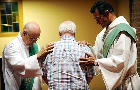 Dcns. Jose Berrios (L) and Salvador Otero pray over John Kenealy.