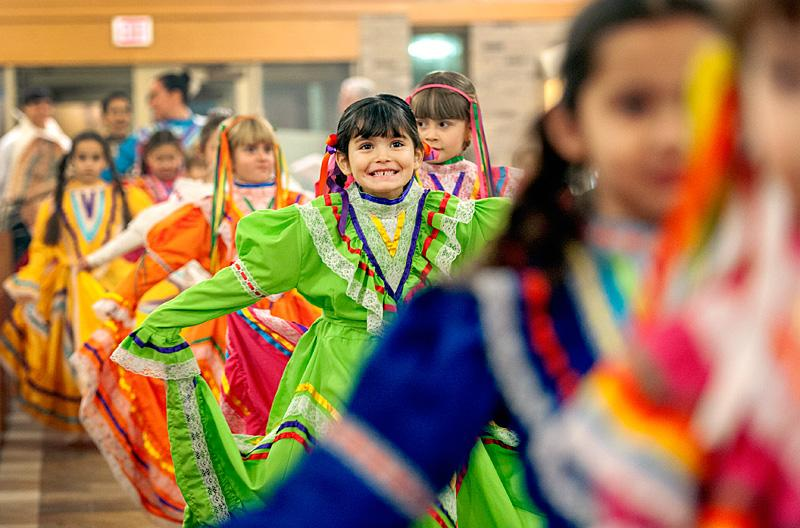 Five-year-old Eliana Menting (center) and other members of the Papalotl Mexican dance group process into Mass.