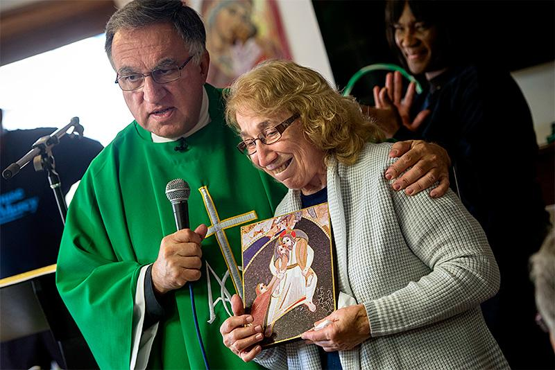 During Mass at the House of Mercy in Rochester Nov. 6, Father Thomas Rosica presents Sister Grace Miller with a gift from Pope Francis in recognition of the ministry's charitable efforts.
