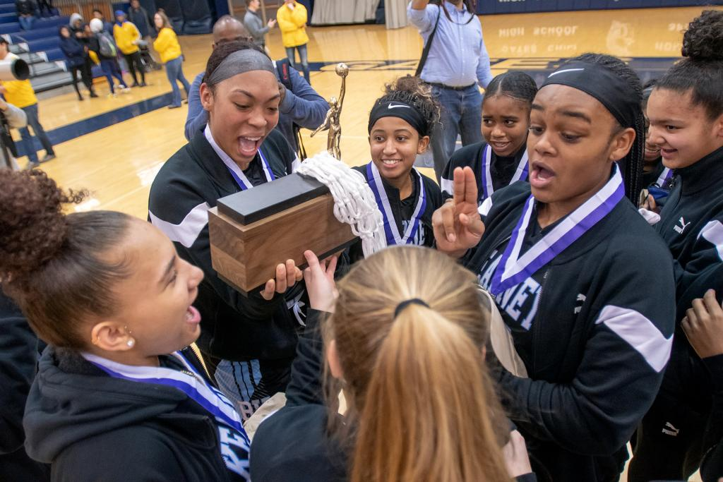 Members of the Bishop Kearney girls' basketball team celebrates with their championship trophy.