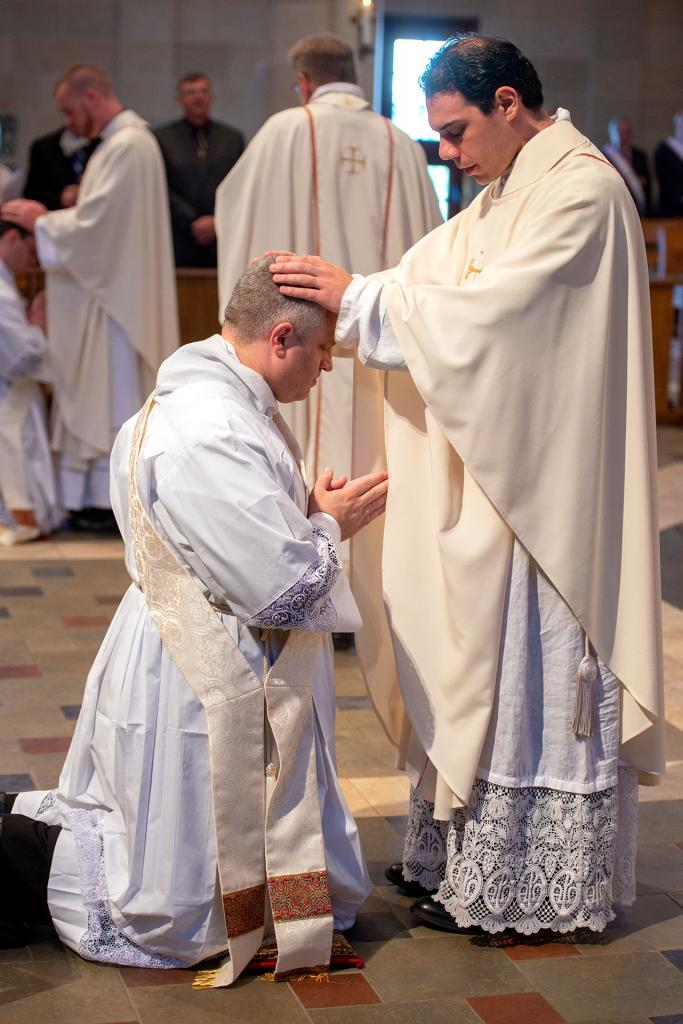 Father Anthony Amato places his hands on the head of Father Lewis.