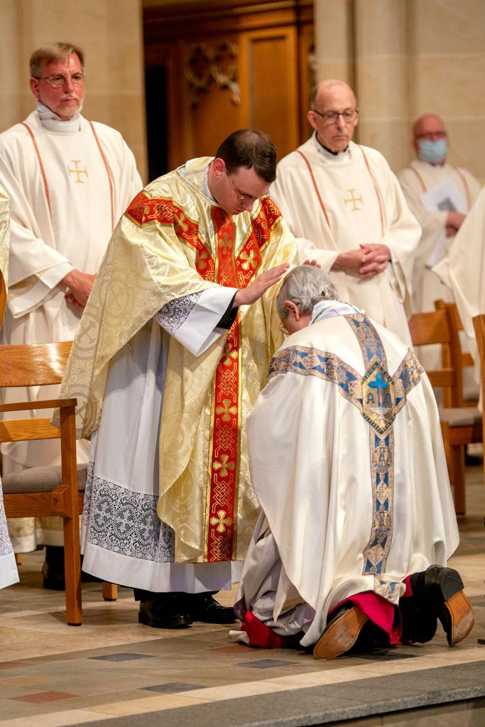 Bishop Matano receives a blessing from Father Maurici at the conclusion of Mass.