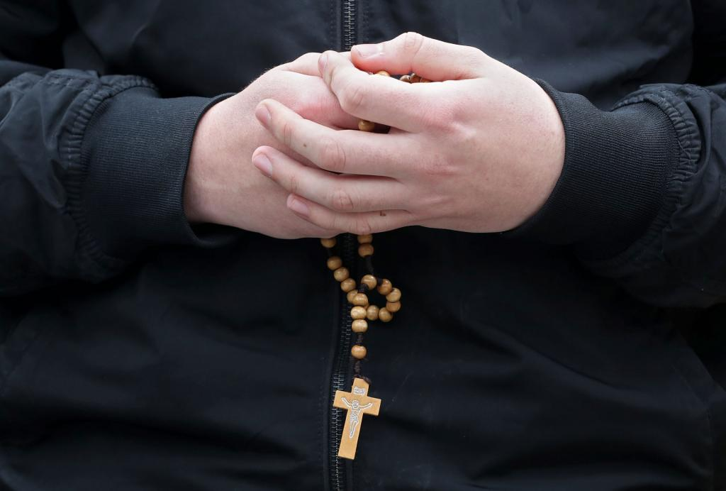 A man holds a rosary outside Notre Dame Cathedral April 16. (CNS photo by Yves Herman, Reuters)