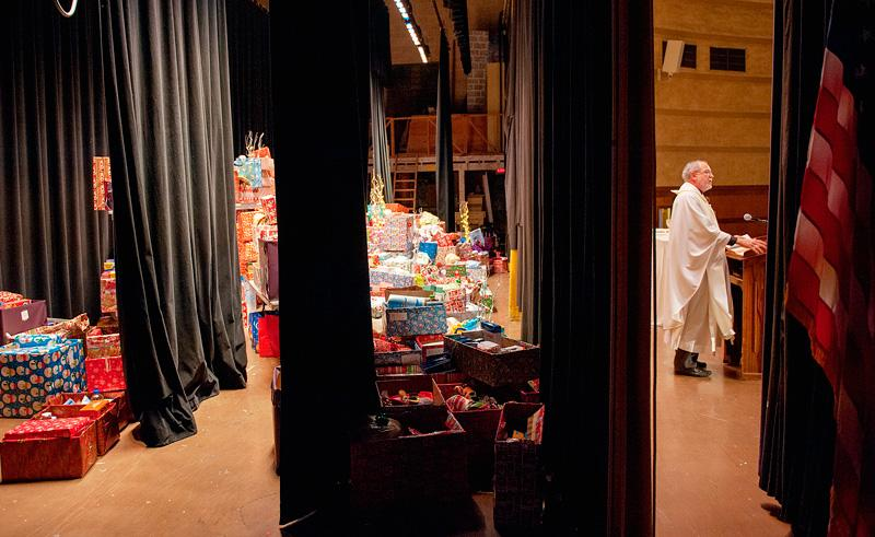 Father Bob Werth delivers the homily as hundred of wrapped gifts wait backstage during the Dec. 20 Golden Mass.