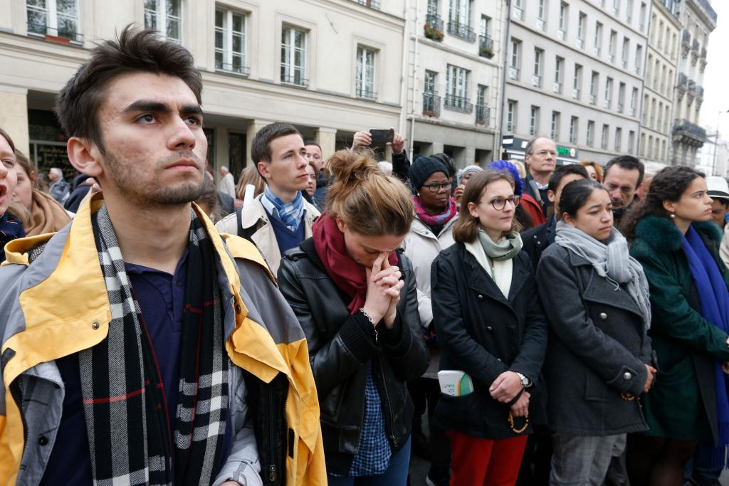 People pray in front of Notre Dame Cathedral April 16. (CNS photo by Paul Haring)