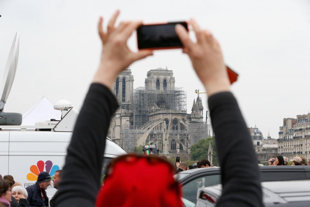 An onlooker takes a cellphone photo of  Notre Dame Cathedral April 16. (CNS photo by Paul Haring)