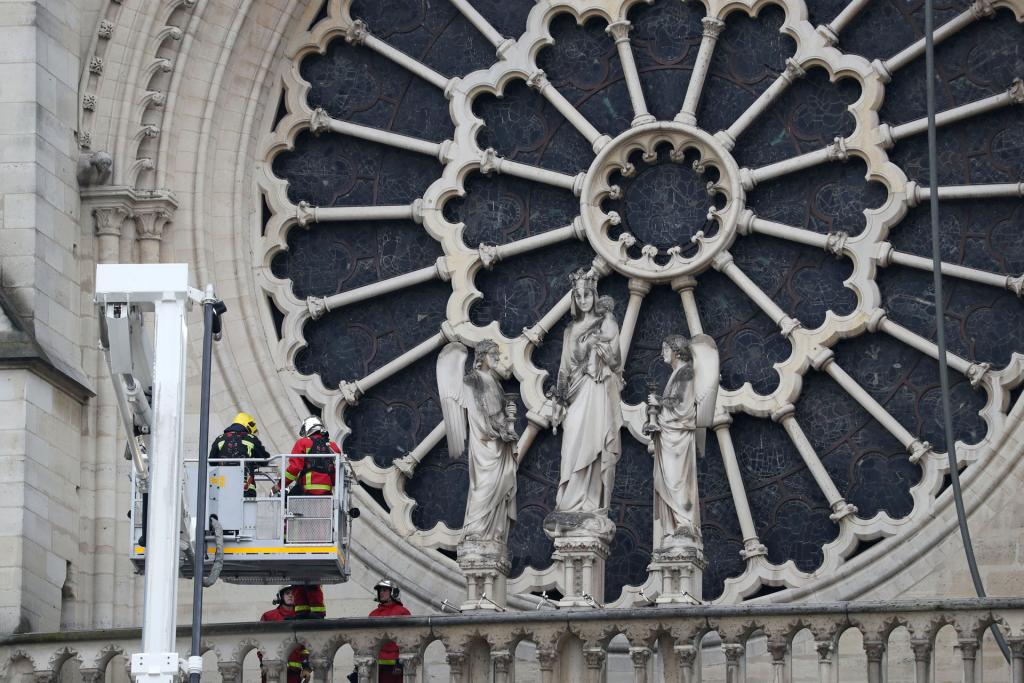Firefighters inspect one of the rosette windows of Notre Dame Cathedral April 16.(CNS photo by Yves Herman, Reuters)