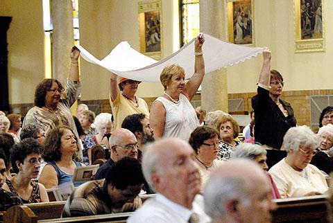Parishioners carry the altar cloth.