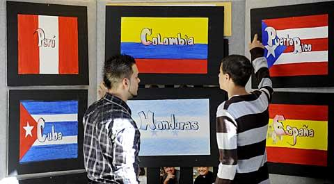Juan Lozada (left) and Kenneth Rodriguez hang posters.