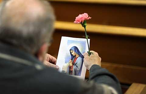 A man holds a flower and a picture of Mary.