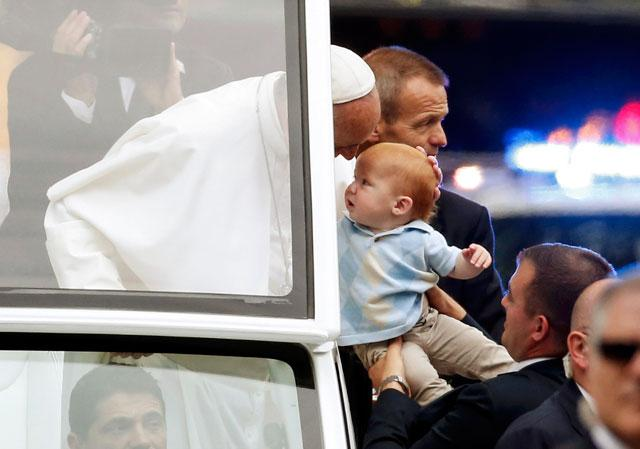Pope Francis blesses a baby from popemobile in Philadelphia