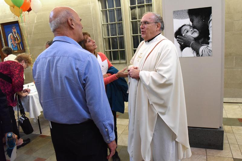 Tom and Annette Basset greet Father James Hewes during a reception after the Diocesan Respect for Life Mass honoring 20 years of Project Rachel ministry at Sacred Heart Cathedral Sunday, Oct. 2.