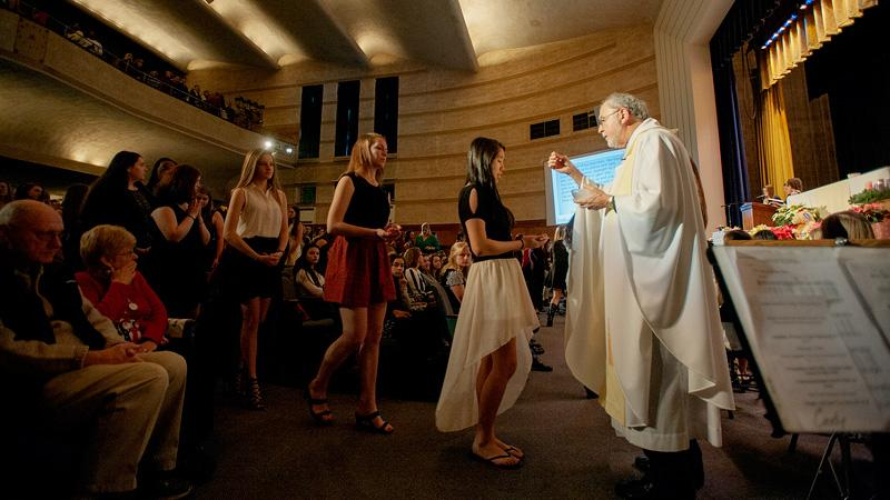 Father Bob Werth gives Communion to Our Lady of Mercy students.