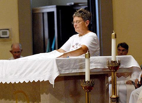 Gail Bauerschmidt helps dress the altar.