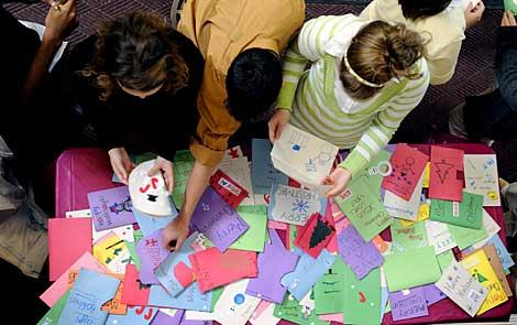 Students select Christmas cards to accompany gifts.