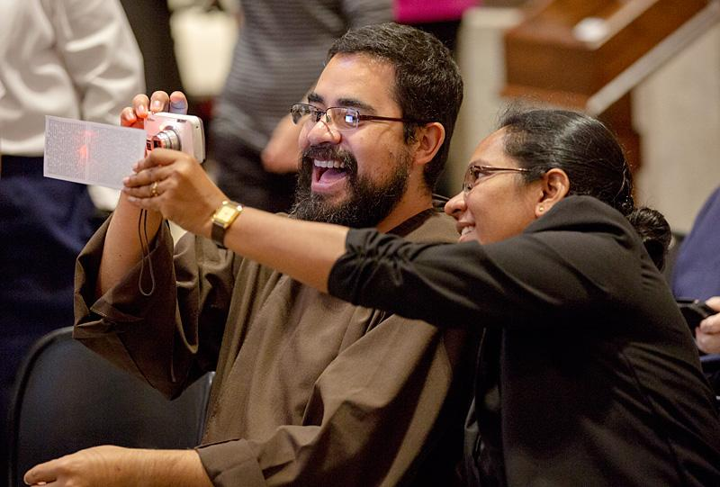 A man takes a picture of his ticket to the evening prayer service at St. Patrick's Cathedral.