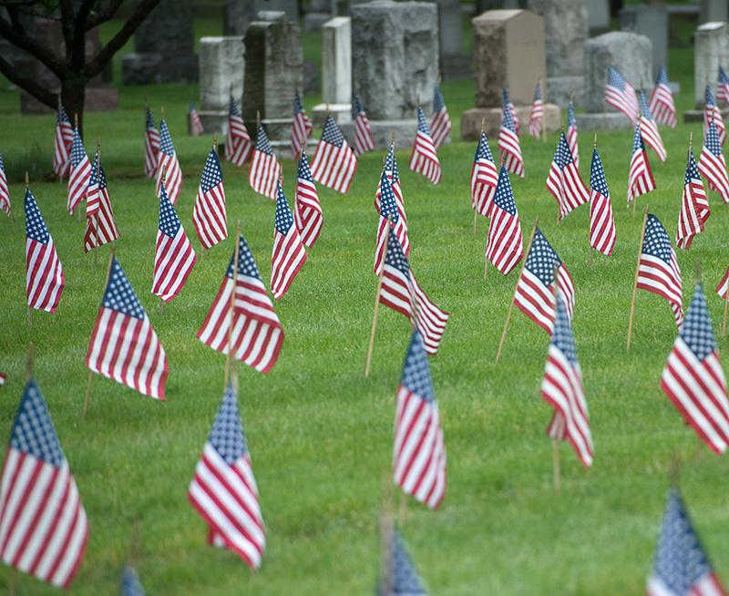 Flags wave in the wind at veterans' headstones in Rochester's Holy Sepulchre Cemetery May 25.