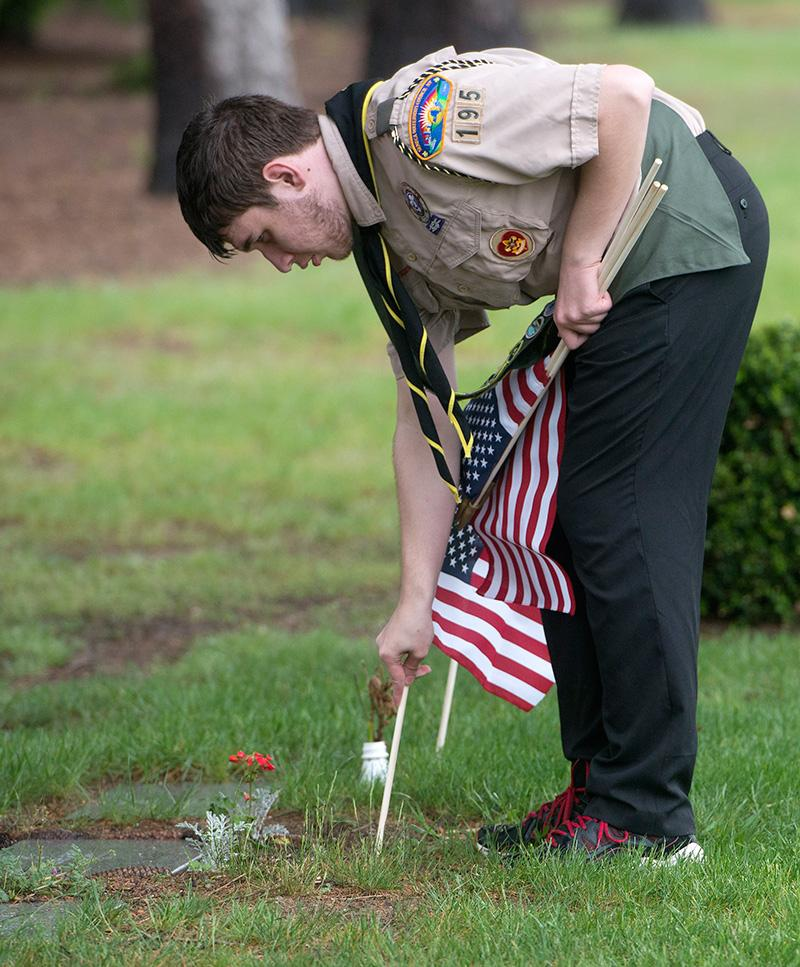 Boy Scout Troop 195 member Peter Burke salutes after placing a flag at a veteran's headstone in Rochester's Holy Sepulchre Cemetery on May 25.
