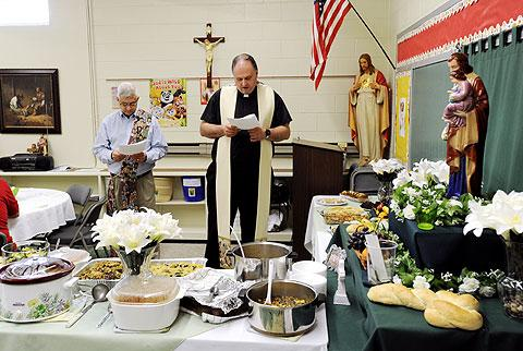 Father Lance Gonyo says a blessing over the food.