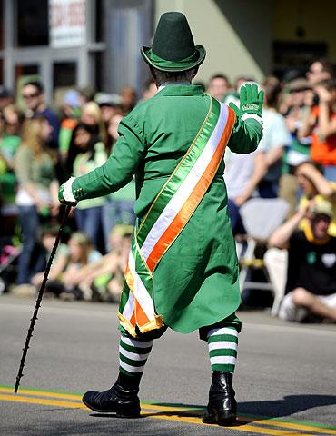 A man dressed as a leprechaun waves to the crowd.