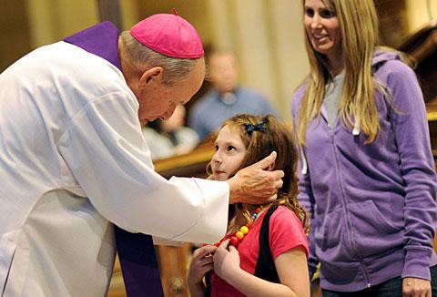Bishop Clark bends down to talk to 8-year-old Julia Resnick.