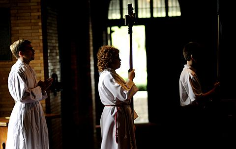 Cross bearer Jenna Caster (center) and others process in.